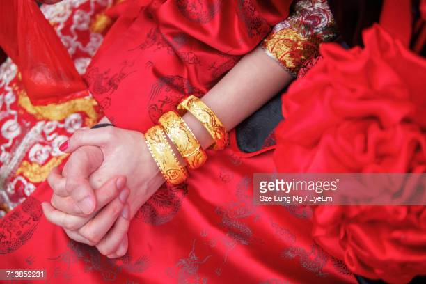 Midsection Of Woman In Red Sari Wearing Gold Bangles