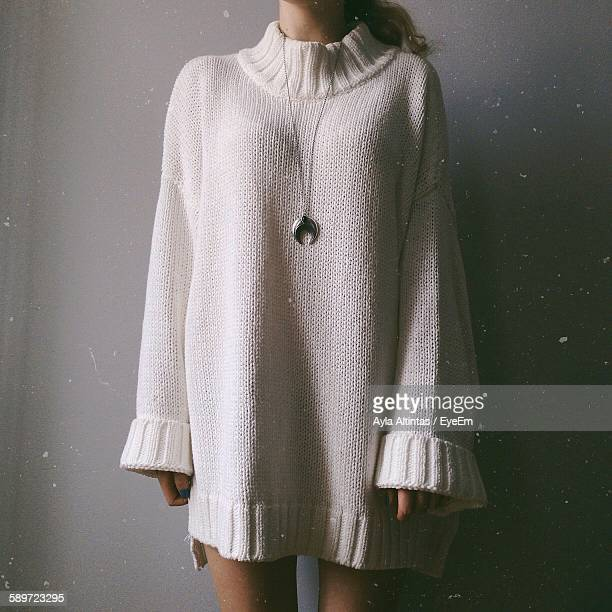 Midsection Of Woman In Sweater Standing Against Wall