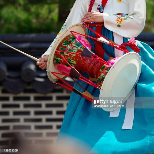 midsection of woman in traditional clothes banging drum outdoors - traditional clothing stock pictures, royalty-free photos & images