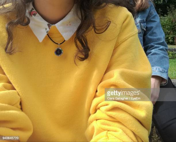 Midsection Of Woman In Yellow Sweater Sitting With Friend