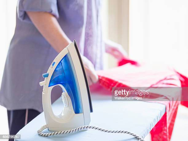 Mid-section of woman ironing shirt