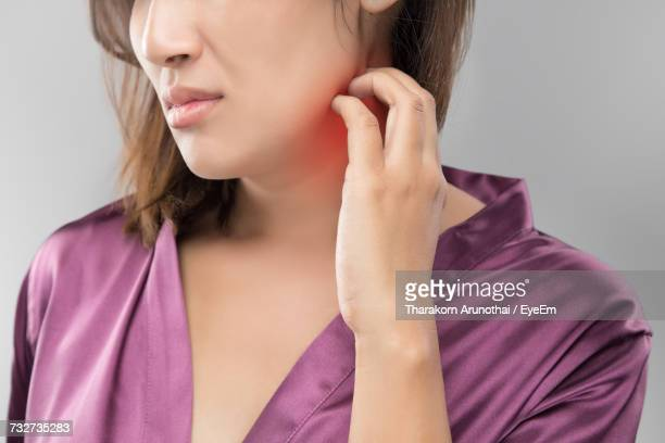 midsection of woman itching on neck - dermatitis fotografías e imágenes de stock
