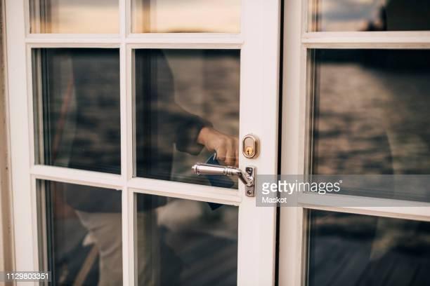 midsection of woman locking glass door at holiday villa - sluiten stockfoto's en -beelden