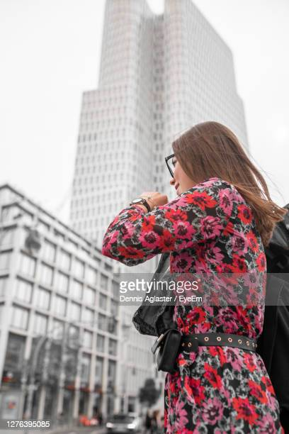 midsection of woman looking at city - one young woman only stock pictures, royalty-free photos & images