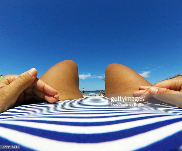 midsection of woman lying at beach against sky - sezione centrale foto e immagini stock
