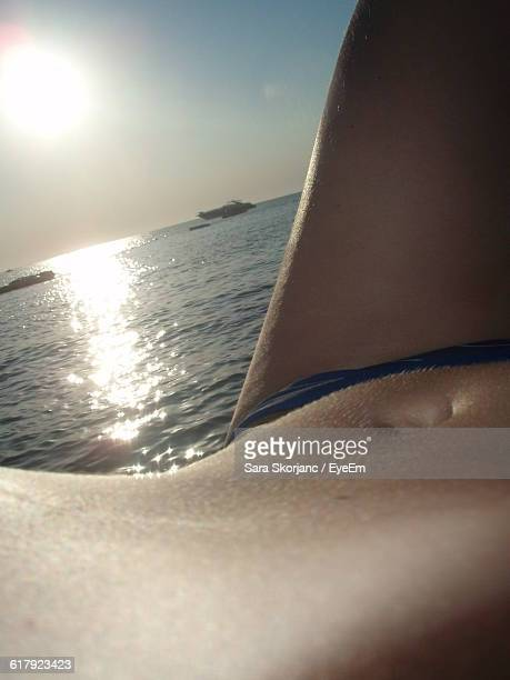 Midsection Of Woman Lying At Beach During Sunset