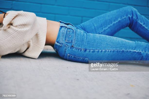 Midsection Of Woman Lying On Footpath
