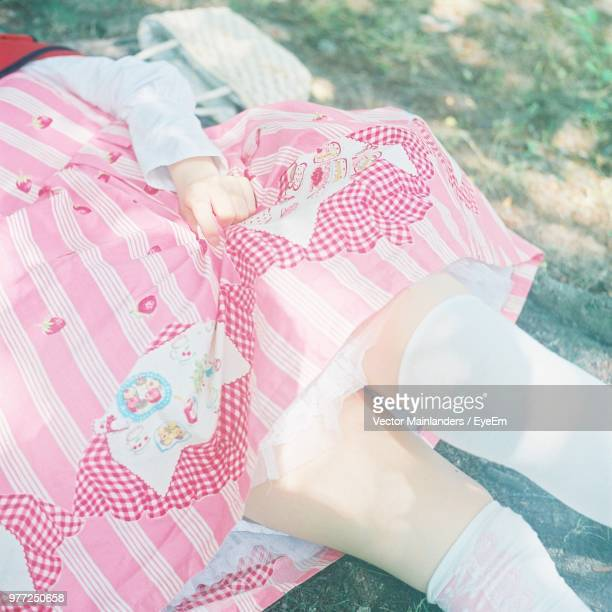 Midsection Of Woman Lying On Grassy Field