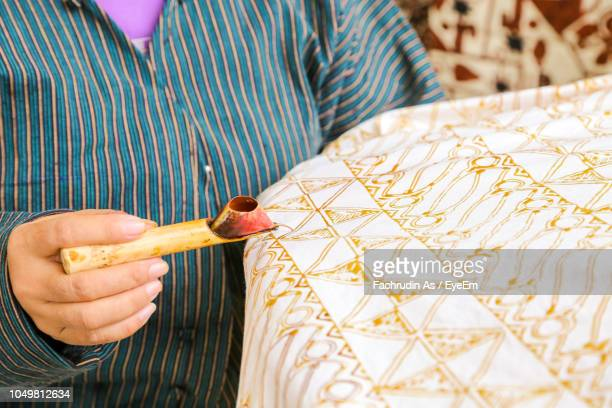 midsection of woman making batik on textile - yogyakarta stock pictures, royalty-free photos & images