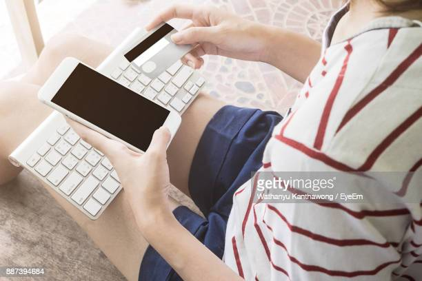 Midsection Of Woman Making Card Payment Through Mobile Phone At Home