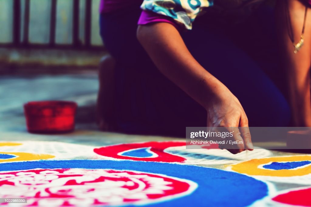 Midsection Of Woman Making Colorful Rangoli : Stock Photo