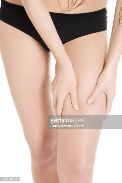 Midsection Of Woman Massaging Thigh Against White Background