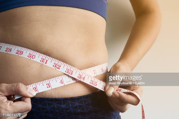 Midsection Of Woman Measuring Belly