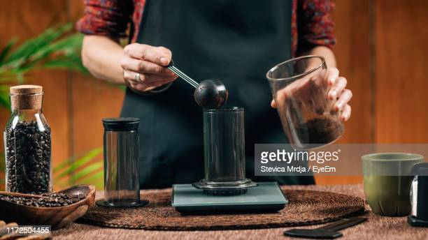 midsection of woman measuring ground coffee in cafe - ground coffee stock photos and pictures