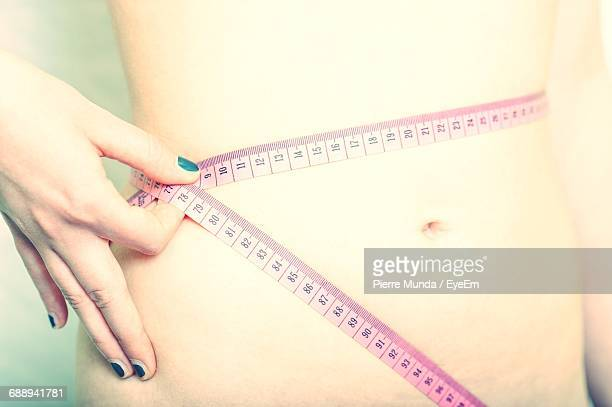 Midsection Of Woman Measuring Her Waist