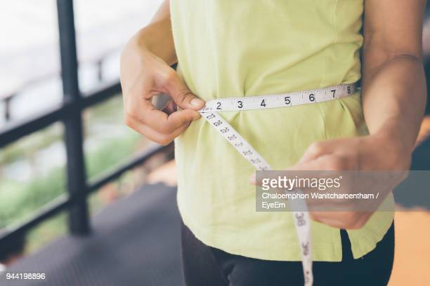 midsection of woman measuring her waist with tape measure - waist stock pictures, royalty-free photos & images
