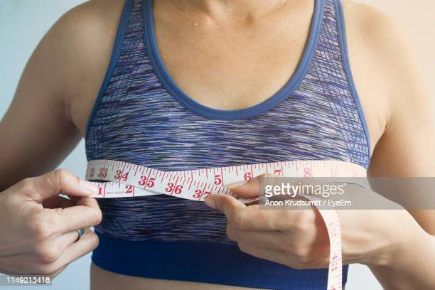 midsection of woman measuring tape measure - bra stock pictures, royalty-free photos & images