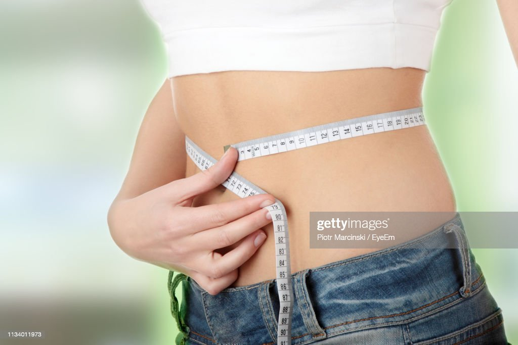 Midsection Of Woman Measuring Waist : Stock Photo