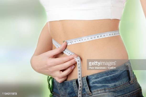 midsection of woman measuring waist - dieting stock pictures, royalty-free photos & images