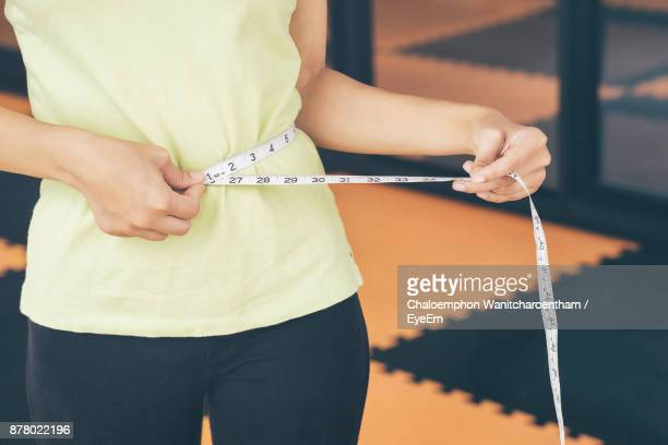 midsection of woman measuring waist - waist stock pictures, royalty-free photos & images