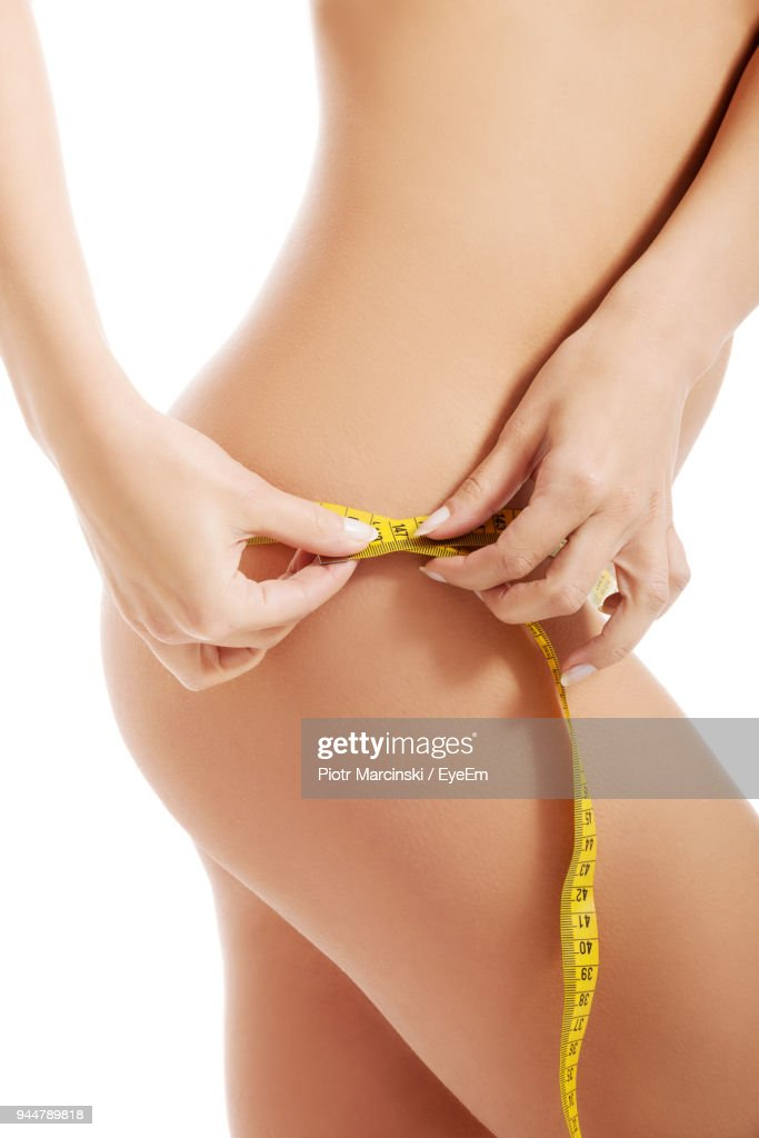 Midsection Of Woman Measuring Waist While Standing Against White Background : Stock Photo