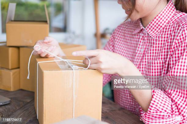 midsection of woman opening box at home - unboxing stock pictures, royalty-free photos & images