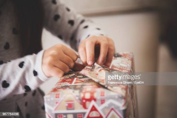 Midsection Of Woman Opening Wrapping Paper On Gift