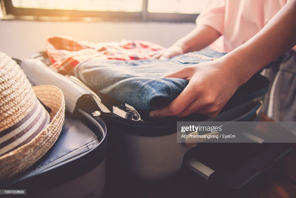 Midsection Of Woman Packing Suitcase At Home : Stockfoto
