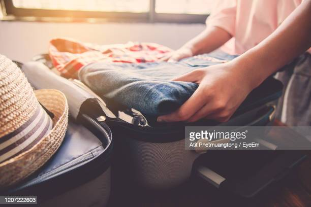midsection of woman packing suitcase at home - packing stock pictures, royalty-free photos & images