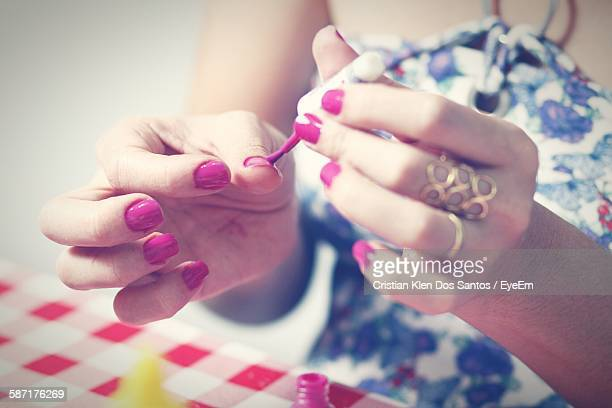 Midsection Of Woman Painting Fingernails
