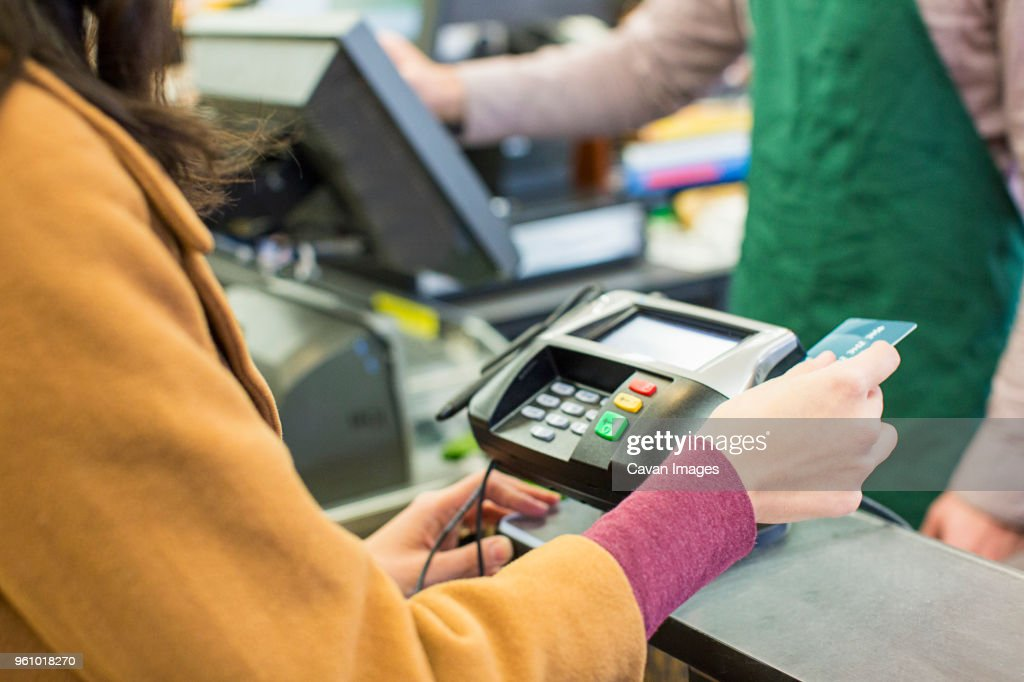 Midsection of woman paying bill with credit card at supermarket : Stock Photo