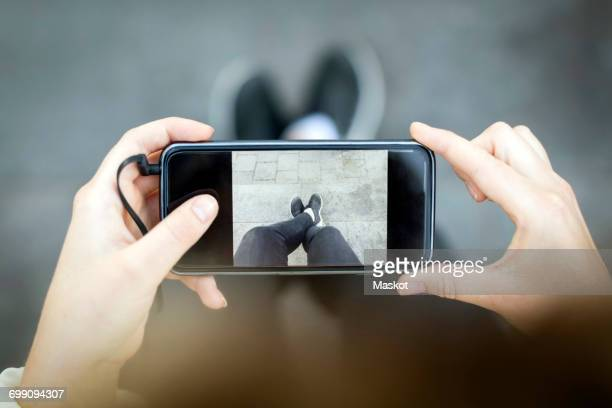 Midsection of woman photographing legs