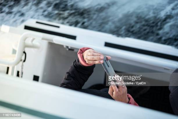 midsection of woman photographing while in nautical vessel on sea - christian soldatke photos et images de collection