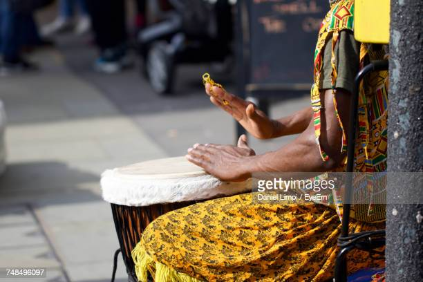 Midsection Of Woman Playing Bongo While Sitting On Chair At Street
