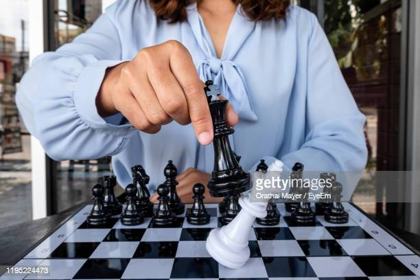 midsection of woman playing chess at home - chess stock pictures, royalty-free photos & images