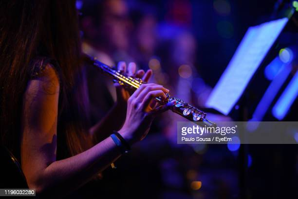 midsection of woman playing flute in music concert - orquestra - fotografias e filmes do acervo