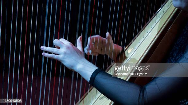 midsection of woman playing harp - stringed instrument stock pictures, royalty-free photos & images