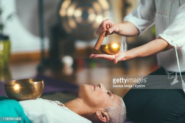 midsection of woman playing singing bowl for customer in spa - gong stock pictures, royalty-free photos & images