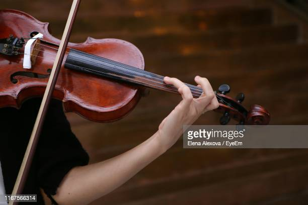 midsection of woman playing violin at home - musical instrument string stock pictures, royalty-free photos & images