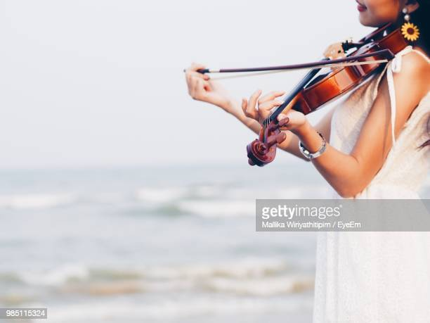 Midsection Of Woman Playing Violin By Sea Against Sky