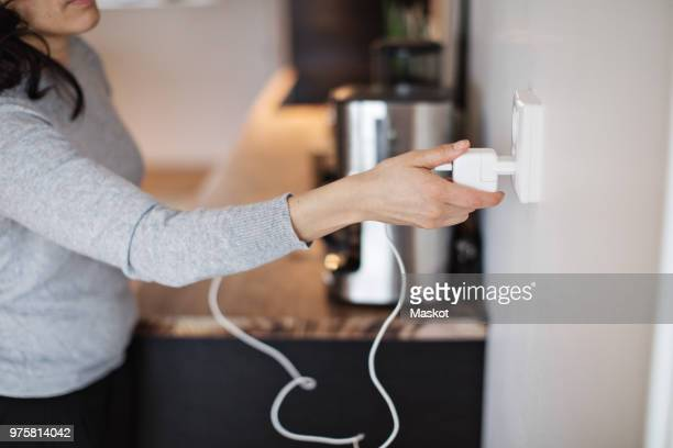 midsection of woman plugging mobile phone charger on wall at home - electricity stock pictures, royalty-free photos & images