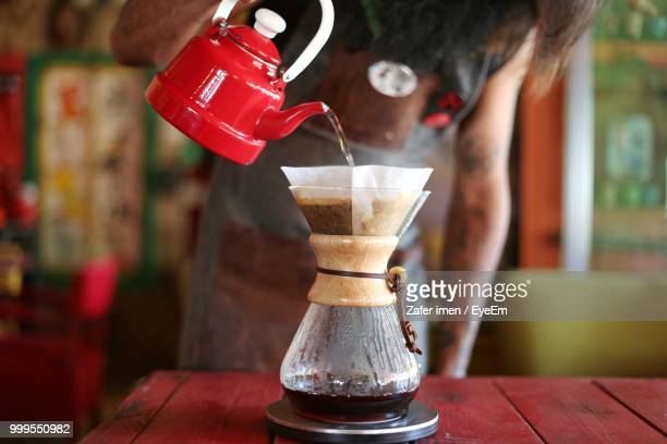 midsection of woman pouring coffee on table - ground coffee stock photos and pictures