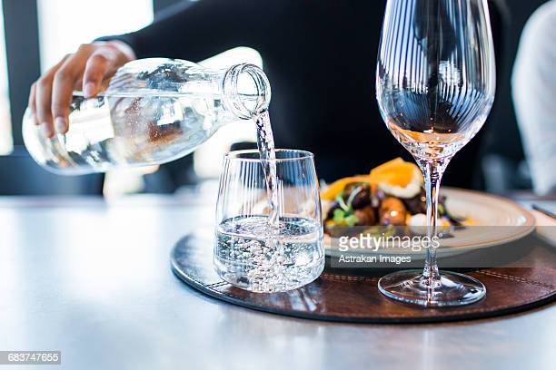 midsection of woman pouring water into glass at restaurant - fülle stock-fotos und bilder