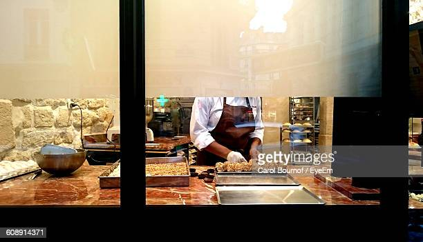 Midsection Of Woman Preparing Desert At Bakery Shop