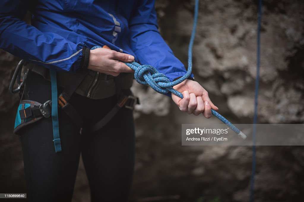 Midsection Of Woman Preparing For Rock Climbing : Stock Photo