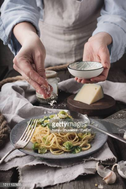 midsection of woman preparing pasta with brussels sprout - pesto stock pictures, royalty-free photos & images
