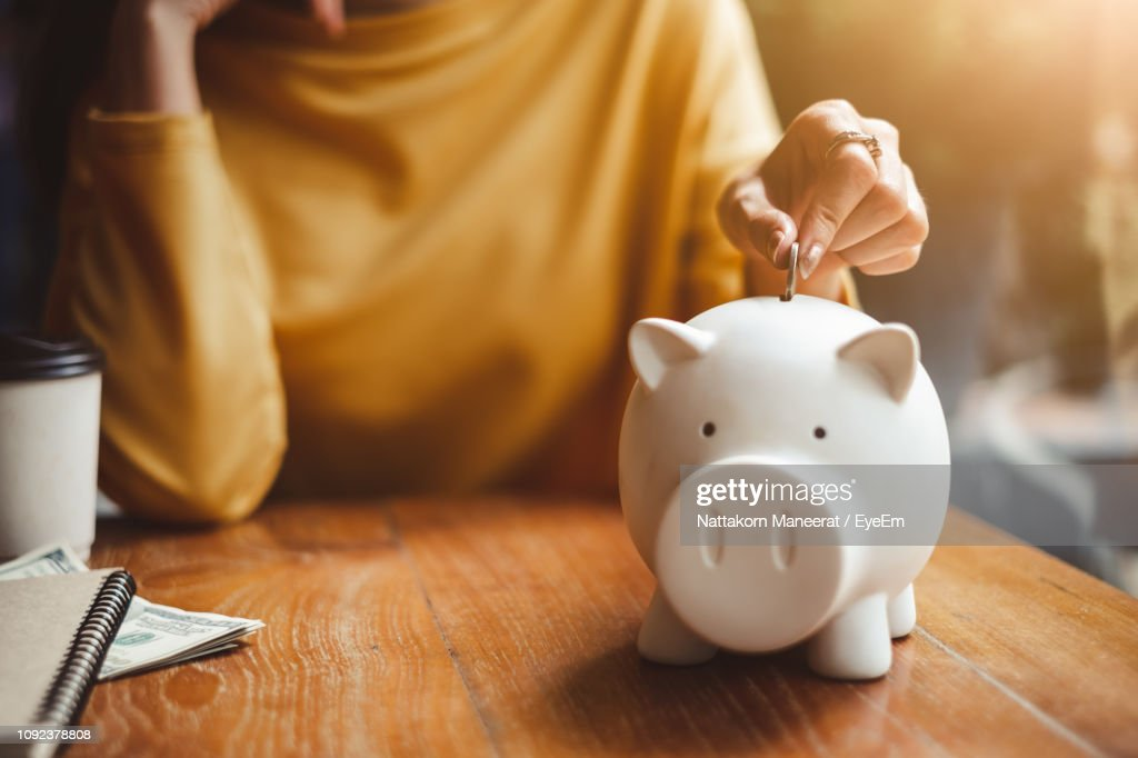 Midsection Of Woman Putting Coin In Piggy Bank On Table At Home : Stock-Foto