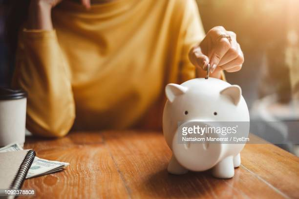 midsection of woman putting coin in piggy bank on table at home - piggy bank stock photos and pictures
