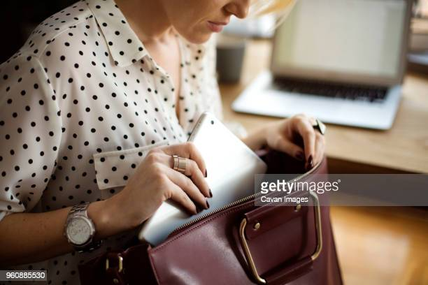 midsection of woman putting tablet computer in purse at home office - bolsa objeto fabricado fotografías e imágenes de stock