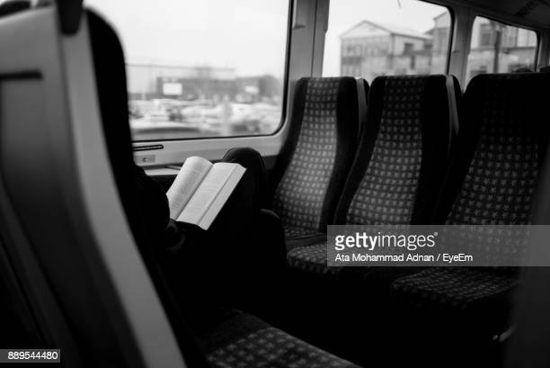 midsection of woman reading book while traveling in train - train interior stock photos and pictures